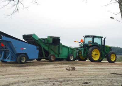 Tractor towing pecan harvesting equipment